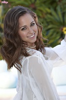 Pornstar Riley Reid posing in a white blouse.