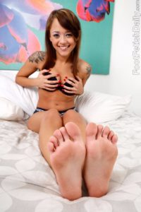 Pornstar Holly Hendrix shows the soles of her feet and her toes.