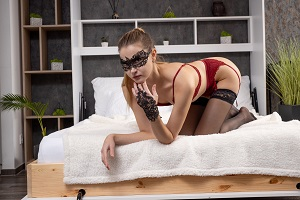 A mask girl in stockings is ready for action in bed.